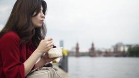 Jovem mulher bonita que come em uma rua alemão no verão, tiro da bandeja filme