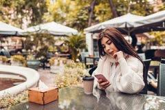 Jovem mulher bonita que come o café no café exterior ao usar o smartphone Retrato da mensagem de datilografia da menina à moda fotos de stock royalty free