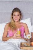 Jovem mulher bonita que come o café da manhã na cama com sócio Foto de Stock Royalty Free