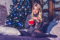Jovem mulher bonita que come a pipoca Jovem mulher bonita na roupa home acolhedor em casa Natal e ano novo imagens de stock royalty free