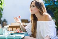 Jovem mulher bonita que come a salada no jardim home Imagens de Stock