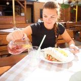 Jovem mulher bonita que come a tortilha mexicana no restaurante imagens de stock royalty free