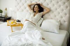Jovem mulher bonita que come um café da manhã na cama Imagem de Stock Royalty Free
