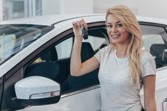 Jovem mulher bonita que compra o carro novo no negócio fotografia de stock