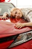 Jovem mulher bonita que compra o carro novo no negócio foto de stock