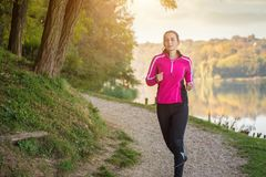 Jovem mulher bonita que corre no lago Fotos de Stock