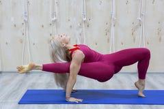 Jovem mulher bonita que dá certo no interior do sótão, fazendo o exercício da ioga na esteira azul fotografia de stock