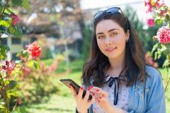 Jovem mulher bonita que datilografa no telefone Rosas no background Copie o espa?o Conceito da tecnologia e do Internet modernos  fotografia de stock royalty free