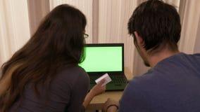 A jovem mulher bonita que deposita em linha pagar taxa em casa usando um portátil com a tela verde e seu noivo fica animado vídeos de arquivo
