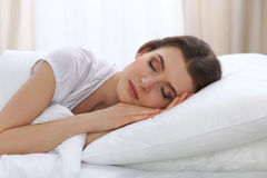 Jovem mulher bonita que dorme ao encontrar-se em sua cama e ao relaxar confortavelmente É fácil acordar para o trabalho ou imagens de stock