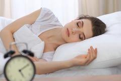 Jovem mulher bonita que dorme ao encontrar-se em sua cama e ao relaxar confortavelmente É fácil acordar para o trabalho ou imagem de stock