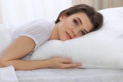Jovem mulher bonita que dorme ao encontrar-se em sua cama e ao relaxar confortavelmente É fácil acordar para o trabalho ou fotografia de stock