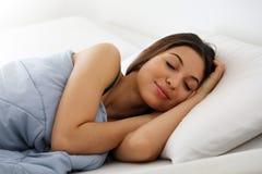 Jovem mulher bonita que dorme ao encontrar-se na cama confortavelmente e alegremente fotografia de stock royalty free