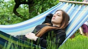 Jovem mulher bonita que dorme em uma rede no jardim, no descanso e em aplanar vídeos de arquivo