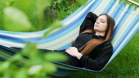 Jovem mulher bonita que dorme em uma rede no jardim, no descanso e em aplanar video estoque