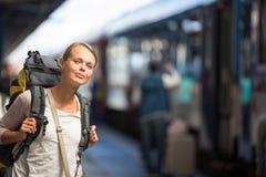 Jovem mulher bonita que embarca um trem/que chega a seu destin Fotos de Stock Royalty Free