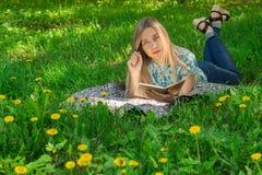 Jovem mulher bonita que encontra-se e que escreve em seu diário na grama com flores Front View imagens de stock