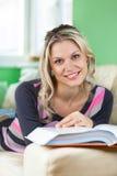 Jovem mulher bonita que encontra-se em um sofá que lê um livro Foto de Stock Royalty Free