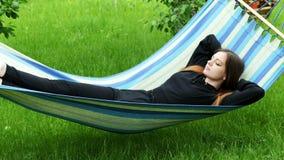 Jovem mulher bonita que encontra-se em uma rede no jardim, no descanso e em aplanar filme