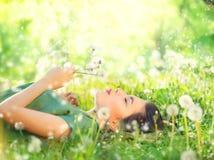 Jovem mulher bonita que encontra-se na grama verde e em dentes-de-leão de sopro imagens de stock royalty free