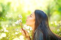 Jovem mulher bonita que encontra-se na grama verde e em dentes-de-leão de sopro Fotografia de Stock