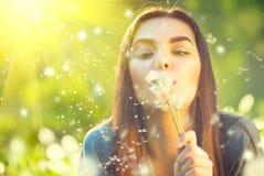 Jovem mulher bonita que encontra-se na grama verde e em dentes-de-leão de sopro foto de stock royalty free