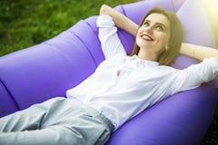 Jovem mulher bonita que encontra-se no lamzac inflável do sofá ao descansar na grama no parque no sol fotos de stock