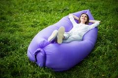 Jovem mulher bonita que encontra-se no lamzac inflável do sofá ao descansar na grama no parque no sol sob o céu imagens de stock royalty free