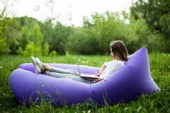 Jovem mulher bonita que encontra-se no lamzac inflável do sofá que trabalha no portátil ao descansar na grama no parque imagens de stock royalty free