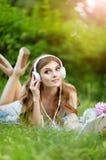 Jovem mulher bonita que encontra-se no prado verde foto de stock royalty free