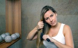 Jovem mulher bonita que endireita o cabelo com a foto de stock royalty free