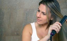 Jovem mulher bonita que endireita o cabelo com a foto de stock