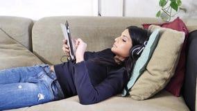Jovem mulher bonita que escuta a música com fones de ouvido vídeos de arquivo