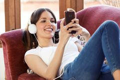 Jovem mulher bonita que escuta a música com fones de ouvido e que usa o telefone celular ao descansar em um sofá em casa imagem de stock royalty free