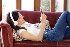 Jovem mulher bonita que escuta a música com fones de ouvido e que usa o telefone celular ao descansar em um sofá em casa imagens de stock