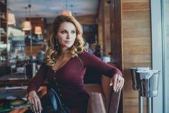 Jovem mulher bonita que espera em um café foto de stock royalty free