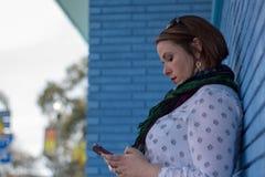 Jovem mulher bonita que está contra texting azul da parede de tijolo imagem de stock