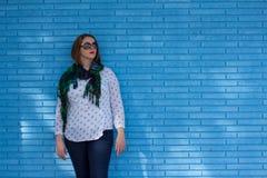 Jovem mulher bonita que está contra uma parede de tijolo azul fotografia de stock