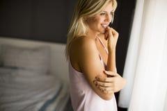 Jovem mulher bonita que está pela janela fotos de stock royalty free