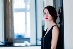 Jovem mulher bonita que está perto da porta no luxo claro Imagem de Stock