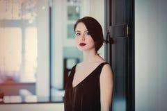 Jovem mulher bonita que está perto da porta no luxo claro Imagens de Stock Royalty Free