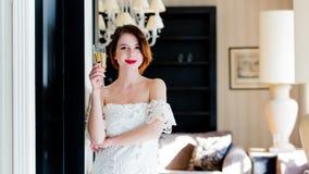 Jovem mulher bonita que está perto da porta no luxo claro Foto de Stock Royalty Free