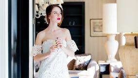 Jovem mulher bonita que está perto da porta no luxo claro Imagem de Stock Royalty Free