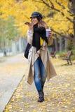 Jovem mulher bonita que fala com as mãos livres do telefone celular ao andar através do parque no outono fotos de stock royalty free