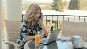 Jovem mulher bonita que fala no telefone ao sentar-se em um restaurante no terraço do verão na frente do portátil