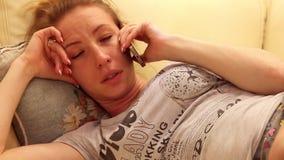 Jovem mulher bonita que fala no telefone e relaxado no sofá dentro vídeos de arquivo