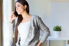 Jovem mulher bonita que fala no telefone em casa Fotografia de Stock Royalty Free