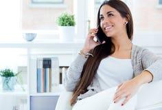 Jovem mulher bonita que fala no telefone em casa Imagem de Stock
