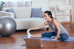 Jovem mulher bonita que faz a ioga em casa imagem de stock