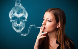 Jovem mulher que fuma o cigarro perigoso com fumo tóxico do crânio Fotografia de Stock